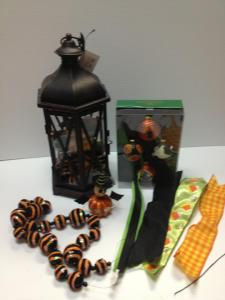 Select and empty lantern and your themed ingredients, here we chose a black lantern for Halloween, Halloween ornaments, ball garland,and fun wired ribbon