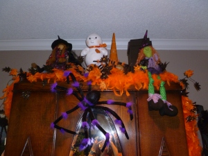Bright orange feather boa, adorns the top of an antiques cabinet. the purple striped spider is crawing down to sample the goodis! the fun collection of green witch, spooky ghost and hats all complete the vignette!