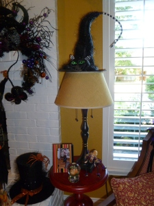 Even the floor lamp is transformed with a witches hat! Tthe black top hat on the hearth adds another detail, along with her collection of sit abouts!