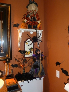 The half bath is painted a burnt orange, a perfect backdrop for halloween. The mice decals attached to the wall add to the creepy crawly feeling of the spiders, bats and witches hats!