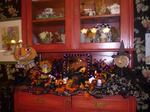 The base of the cabinet serves as another are to display more witches, a pumpkin head man and cute Halloween glass plates!