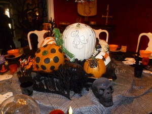 Gina's round dining table is set, her centerpice is filled with faux pumpkins she painted and embellished. the ghostly grey table runner grounds the vignette, dont let the creepy skull scare you away!