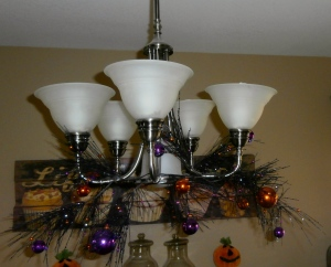The first step is to clean your light fixture while the ladder is out! Then add the garland, and intwine on the arms of the chandelier, pulling some of the branches up and down. Then add one garland from the ceiling down the chain, winding around.