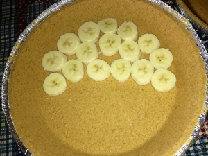 Slice bananas and cover bottom of crust (about 2 small bananas per pie)