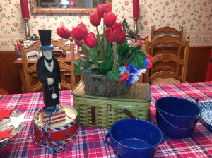 Metal picnic basket elevates the red tulips with a red, white and blue floral garland tucked in.