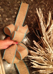 Tie bow and add a longer tail to work around the wreath
