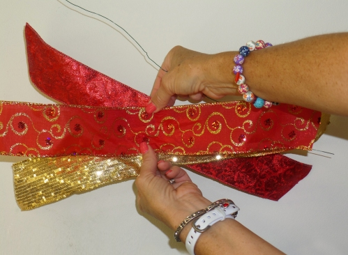 Layer ribbon strips red, gold and patterened red/gold swirl on top.