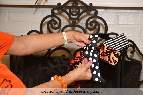 Make a loop of orange and black, and add a stripe black and white ribbon loop, secure with a floral wire, tie a strip of Black and White polka dot over the middle.