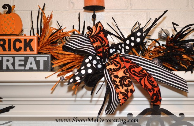 3 ribbon patterns combined in a half bow are a great finishing touch to the mantel garland.