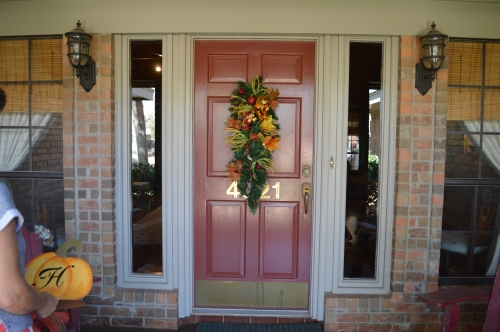 Faux pine teardrop and fall foliage teardrop are wired together fall doorway decor.