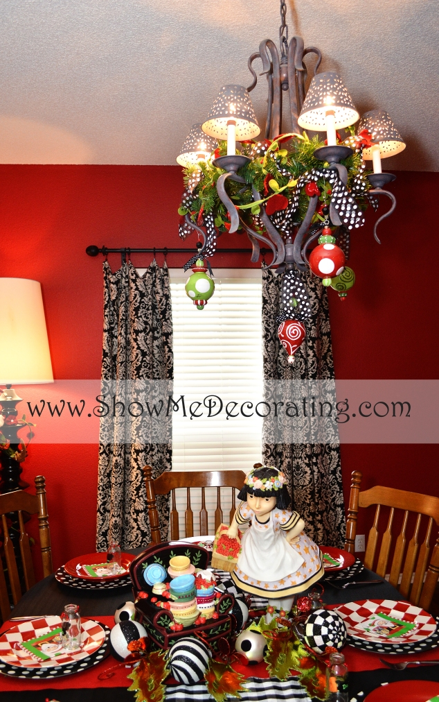 A chandelier is a great place to decorate, faux green garland, red, green and white balls are hung with black and white polka dot ribbon