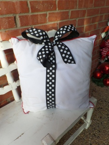 Add polka dot ribbon and tie a shoe string bow, finished on top of the pillow